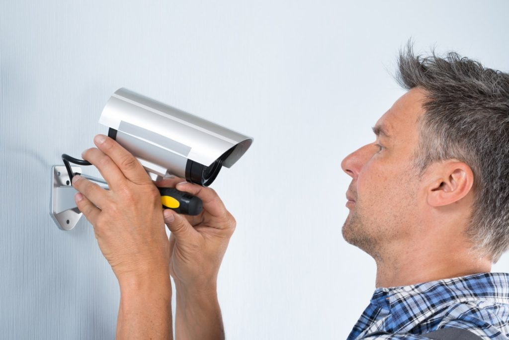мужчина прикручивает камеру